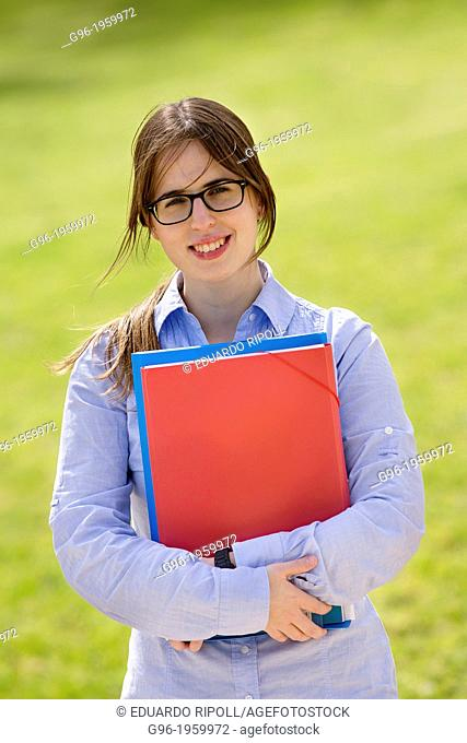 Young student girl at the park with books