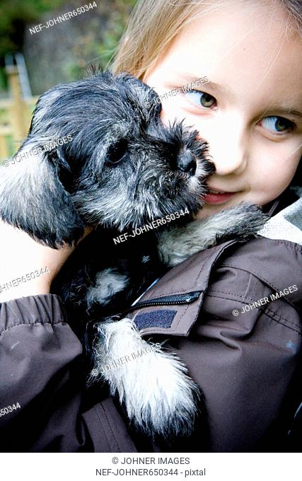 A girl holding a puppy