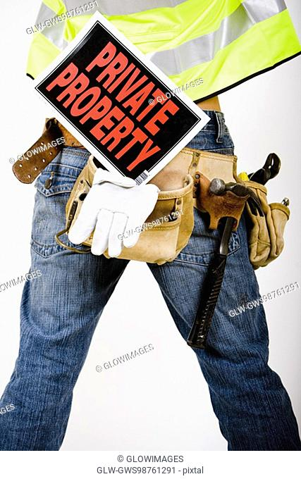 Mid section view of a man wearing a tool belt with a Private Property sign
