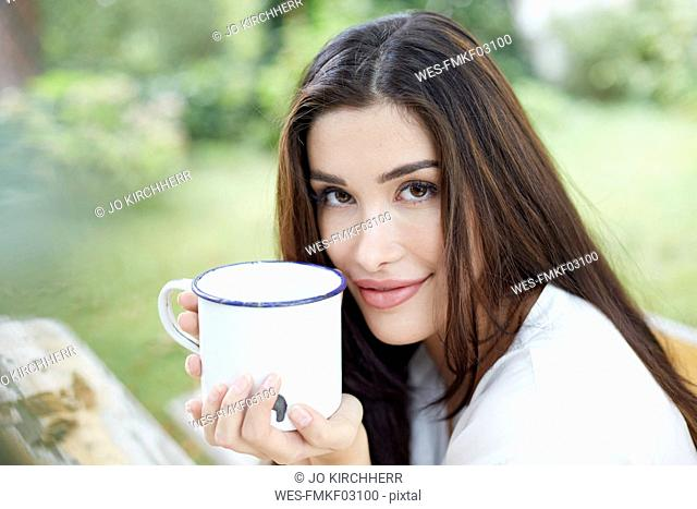 Portrait of smiling woman relaxing with cup of coffee