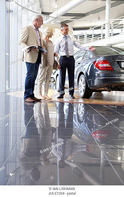Salesman showing couple with brochure car in car dealership showroom