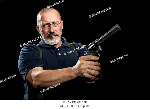 Mature man with holding a revolver