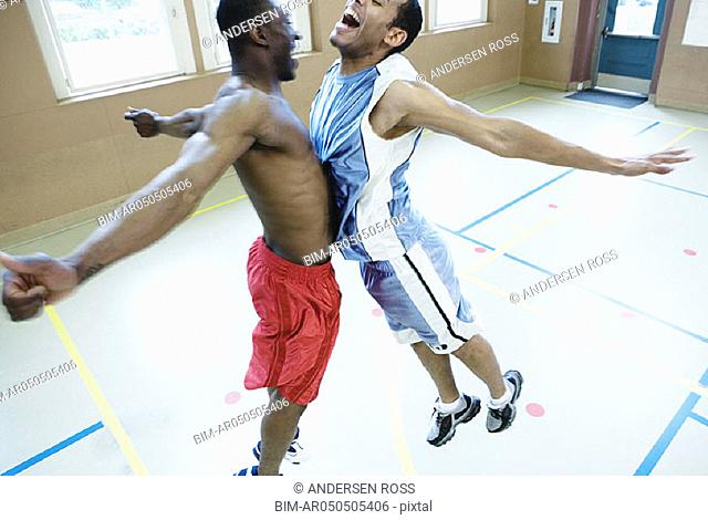 Two basketball players hitting chests together