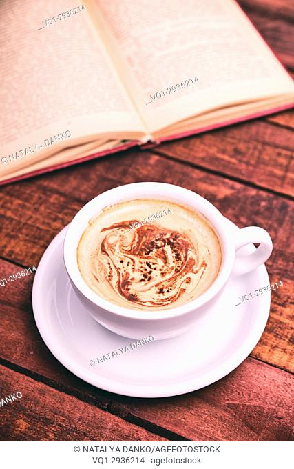 white cup with coffee, behind an open book, top view