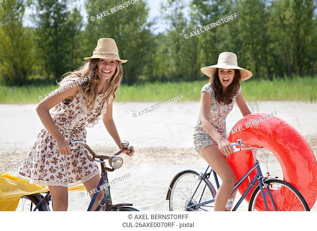 Two pretty women cycling on the beach