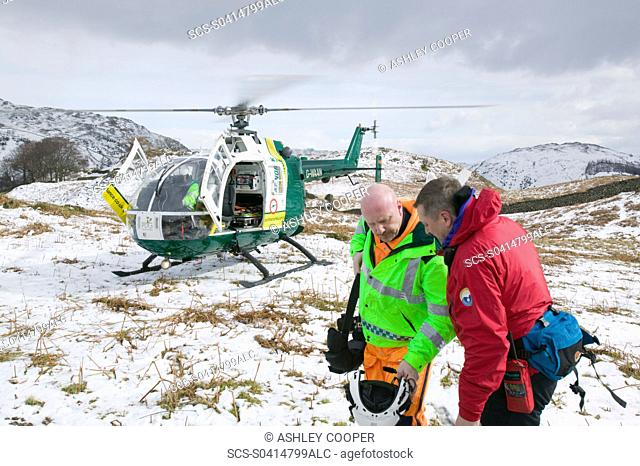 An air ambulance attending a mountain rescue incident in the Lake District near Grasmere UK