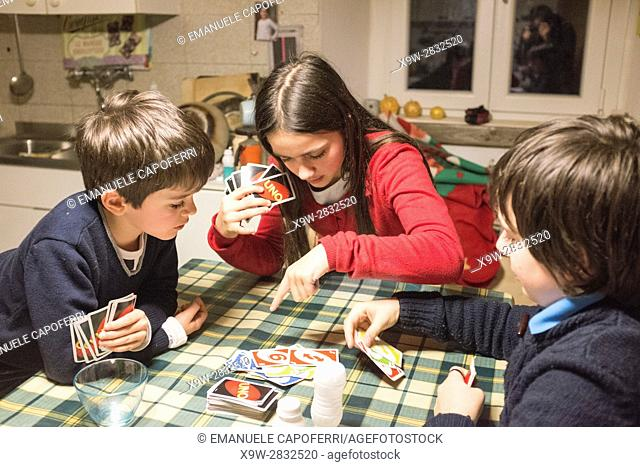 Children play cards at home at the kitchen table