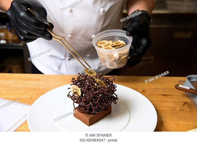Chef placing slices of dried banana on chocolate nest cake decoration