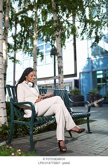 Businesswoman Using PDA on Bench