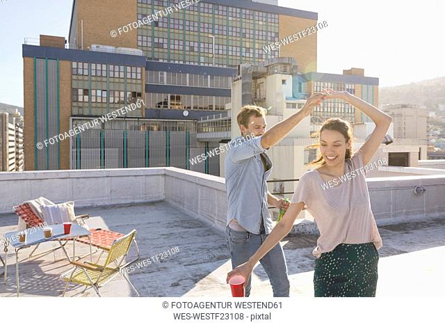 Young couple celebrating on a rooftop terrace, dancing together