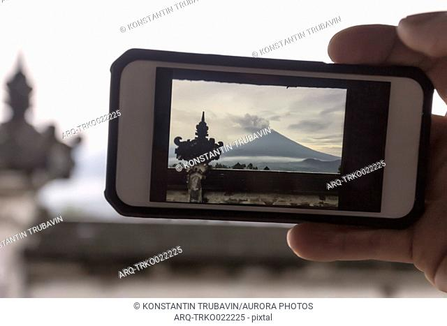 View of photograph on smartphone screen of Mount Agung volcano and Lempuyang temple, Bali, Indonesia