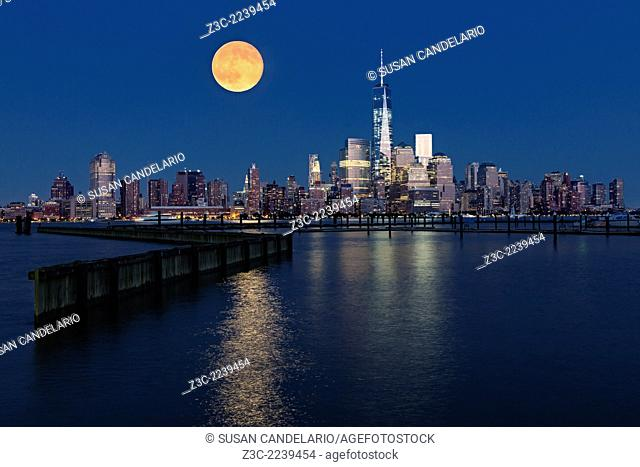 The super moon rises over the lower Manhattan skyline along One World Trade Center commonly referred to as the Freedom Tower during twilight