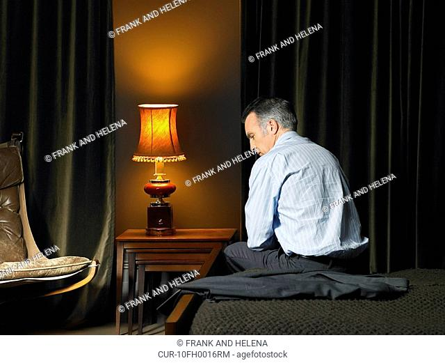 Man sitting on bed with back to camera, looking disappointed