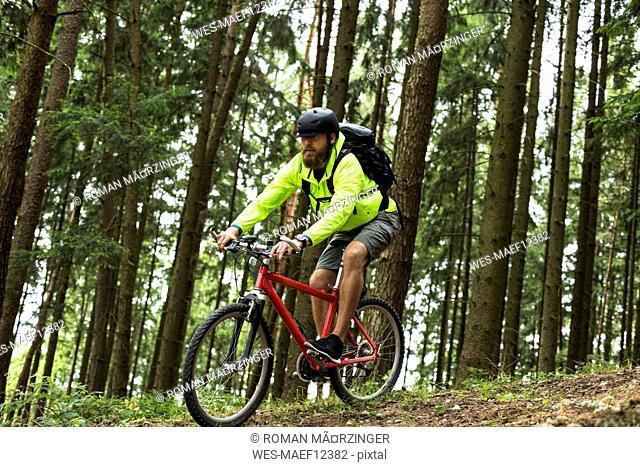 Man mountain biking in forest