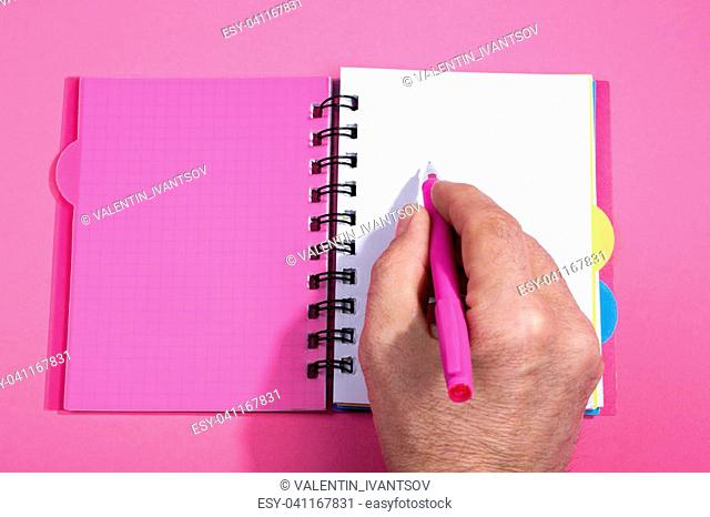 Hand with a pen over an open notebook