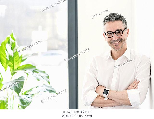 Portrait of smiling businessman wearing smartwatch and glasses
