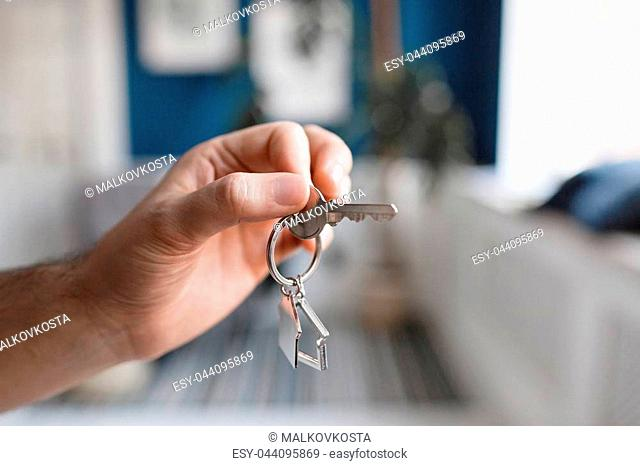 House key and keychain in the form of homes lies on wooden boards. Concept for real estate, moving home or renting property. Copy space