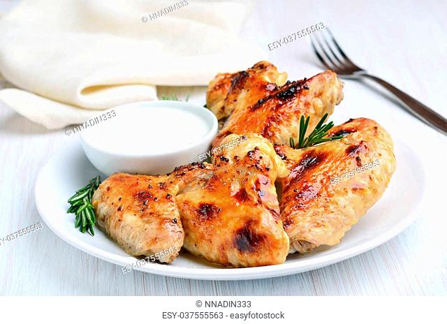 Roasted chicken wings with sauce on white plate