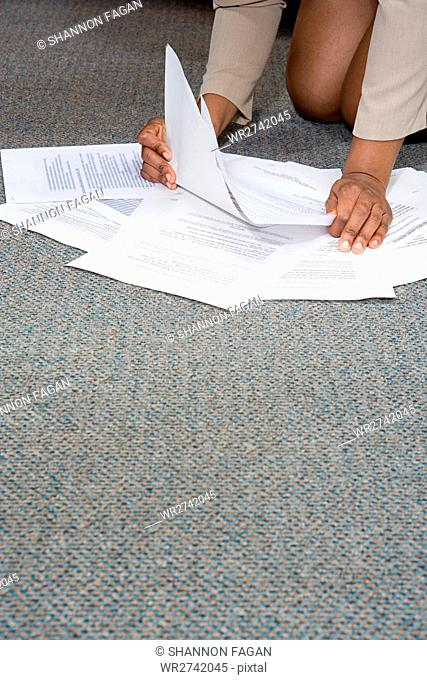 Woman with paperwork on the floor