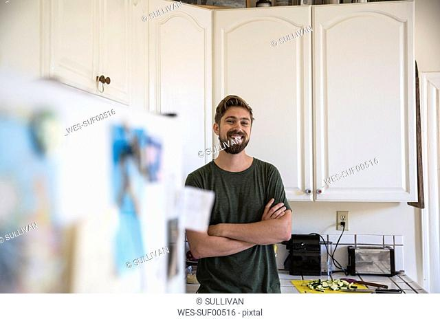 Portrait of smiling man in kitchen at home