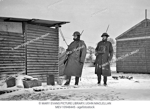 Two soldiers at a camp in winter