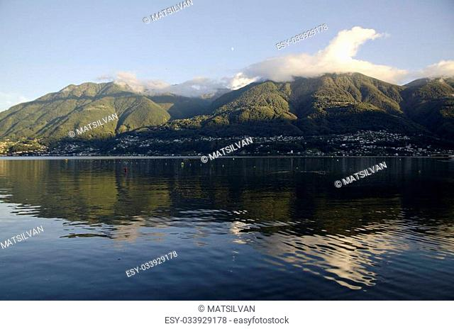 Mountain and clouds with blue sky over an alpine lake