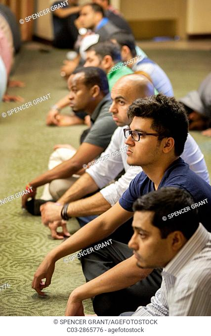 Listening to an Iman's sermon or Khutbah, Muslim men gather for Friday afternoon prayers during religious services at an Anaheim, CA, mosque