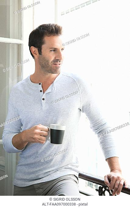 Man looking out of window with mug in hand
