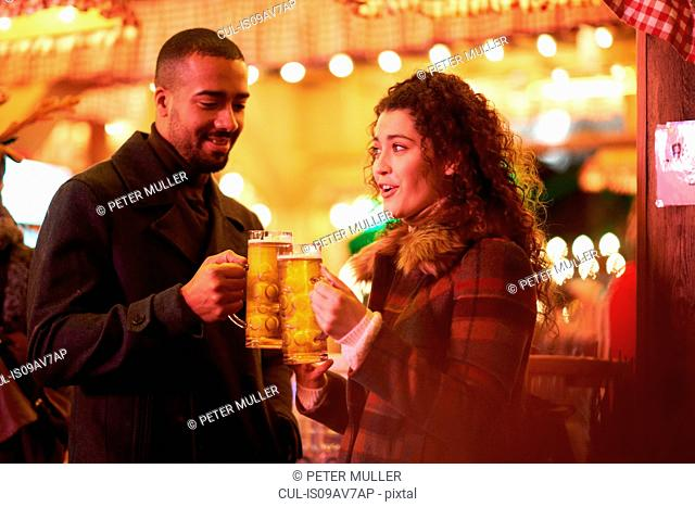 Couple on night out holding glass on beer making a toast