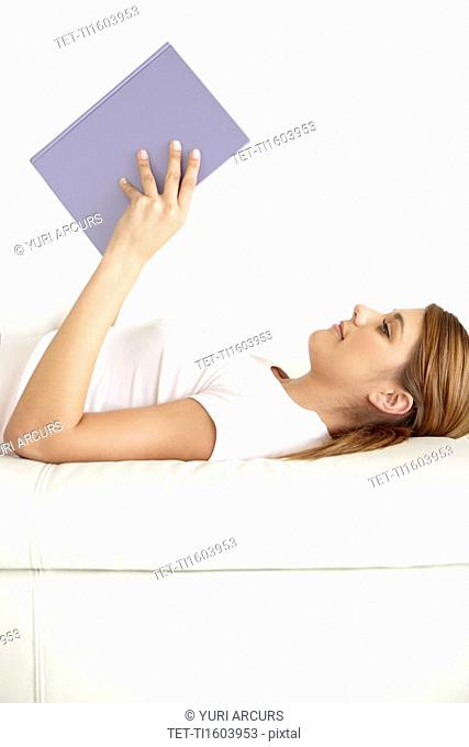 Young woman lying on bed and reading