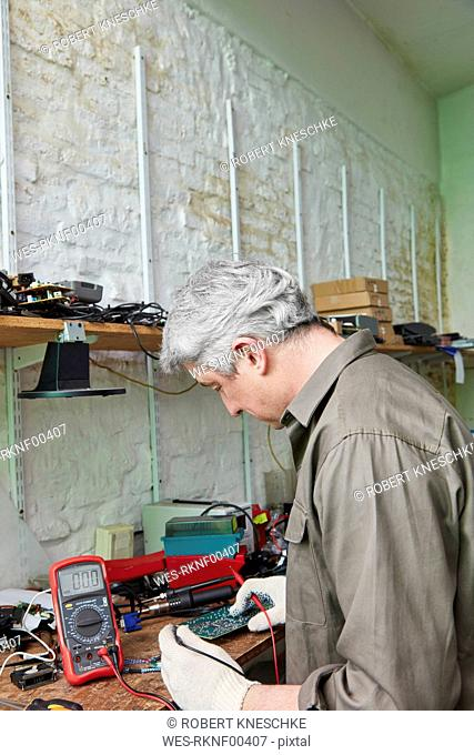 Worker in computer recycling plant soldering motherboard