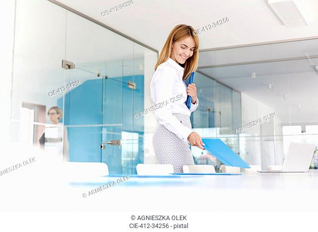 Smiling businesswoman placing folders on conference room table