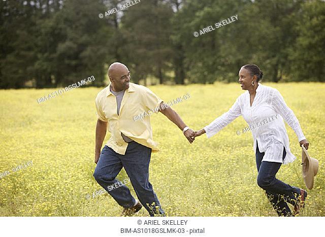 Couple running through field holding hands
