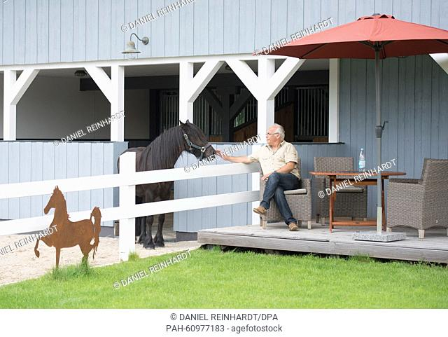 Walter Kau, head of business of Skandwood-Horsehouse GmbH on the terrace of his specia 'Horse House' near to a special stall area