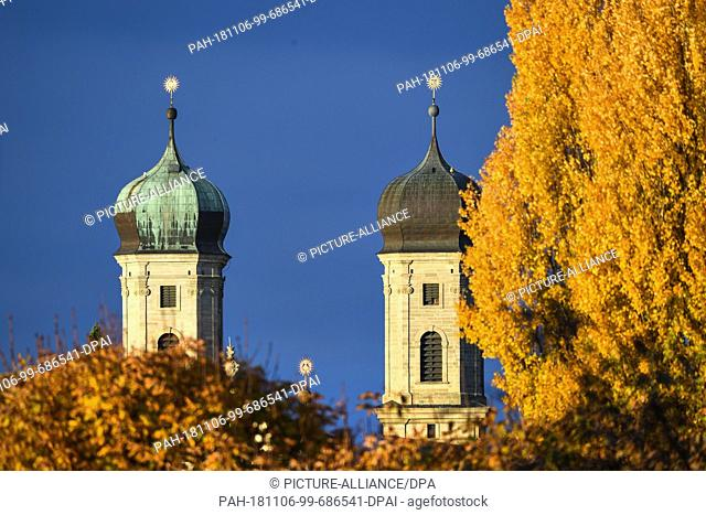 06 November 2018, Baden-Wuerttemberg, Friedrichshafen: The two bell towers of the castle church can be seen behind autumn-coloured trees