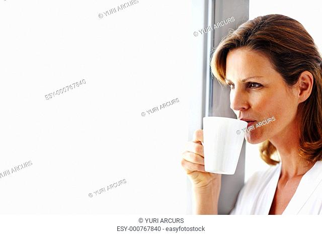 Closeup portrait of cute young lady drinking coffee at home