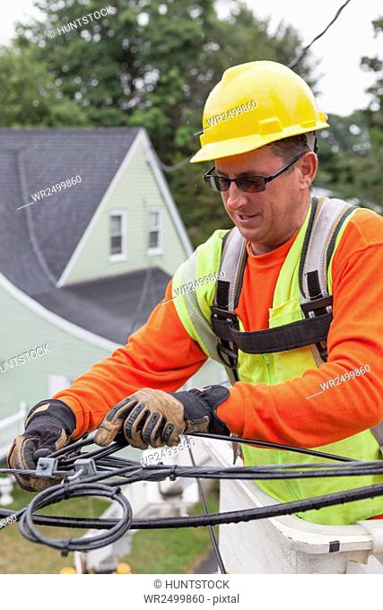 Cable lineman securing cable from house in a bucket truck
