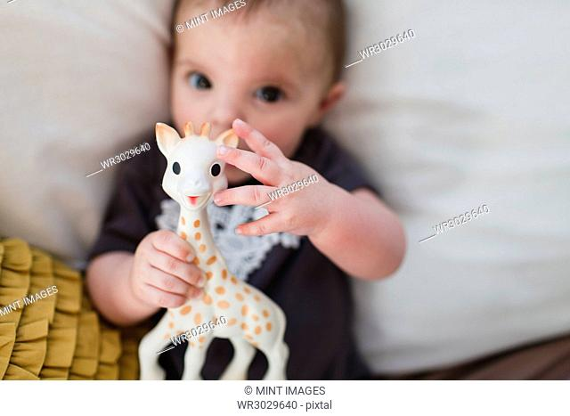 Baby lying on a bed and holding a toy giraffe