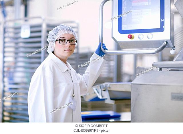 Factory worker wearing hair net looking at camera