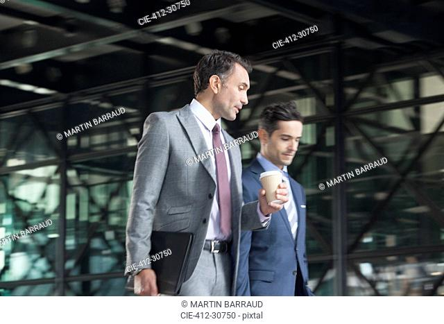 Corporate businessmen with coffee talking and walking