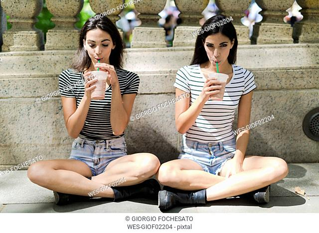 Two twin sisters sitting outdoors having a takeaway drink