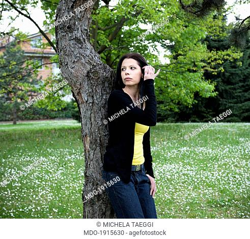 Woman leaning on a tree trunk in the garden and tidying her hair behind the ear. Desio (Italy), 18th April 2014