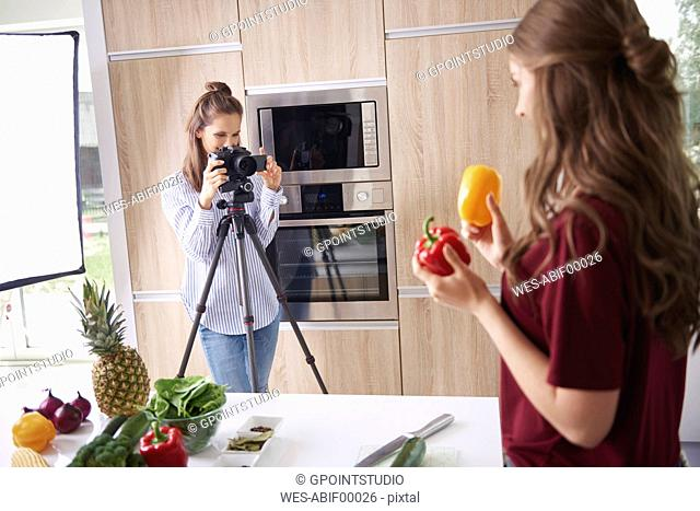 Woman recording friend while preparing healthy food