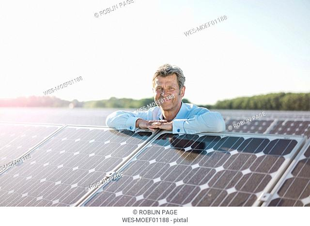 Smiling mature man standing in solar plant