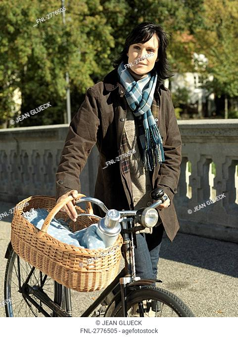 Mature woman walking with bicycle on bridge
