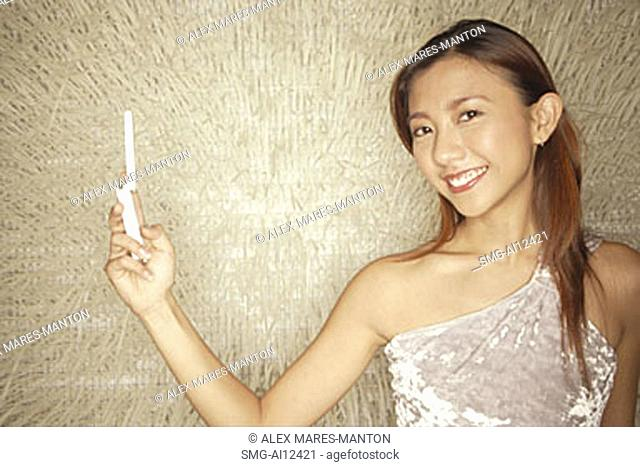 Young woman holding mobile phone, looking at camera