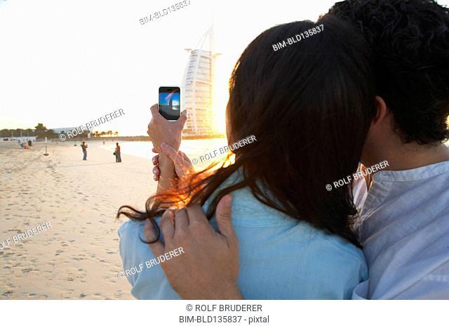 Couple taking pictures together on beach, Dubai, United Arab Emirates