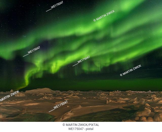Northern lights over the shore of the frozen Disko Bay. Town Ilulissat at the shore of Disko Bay in West Greenland. The icefjord nearby is listed as UNESCO...