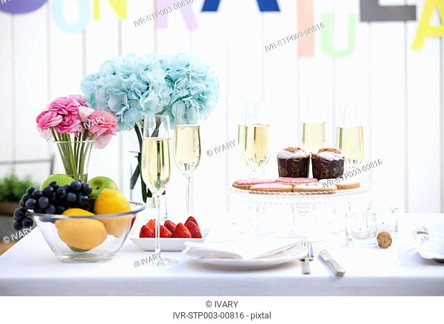 Close-up of wine glass with fruits and cake on table