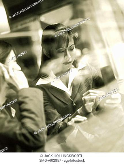 Female executives using PDA and cellular phone seen through glass window